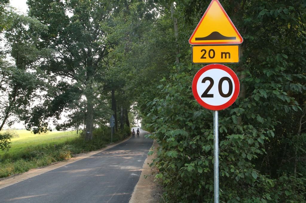 Przebudowany odcinek drogi prowadzący przez pola i las. Na pierwszym planie znak drogowy ostrzegający o progu spowalniającym, który pojawi się na drodze za 20 metrów od miejsca ustawienia znaku oraz znak ograniczenia prędkości do 20 km na godzinę. Zadrzewione pobocze.