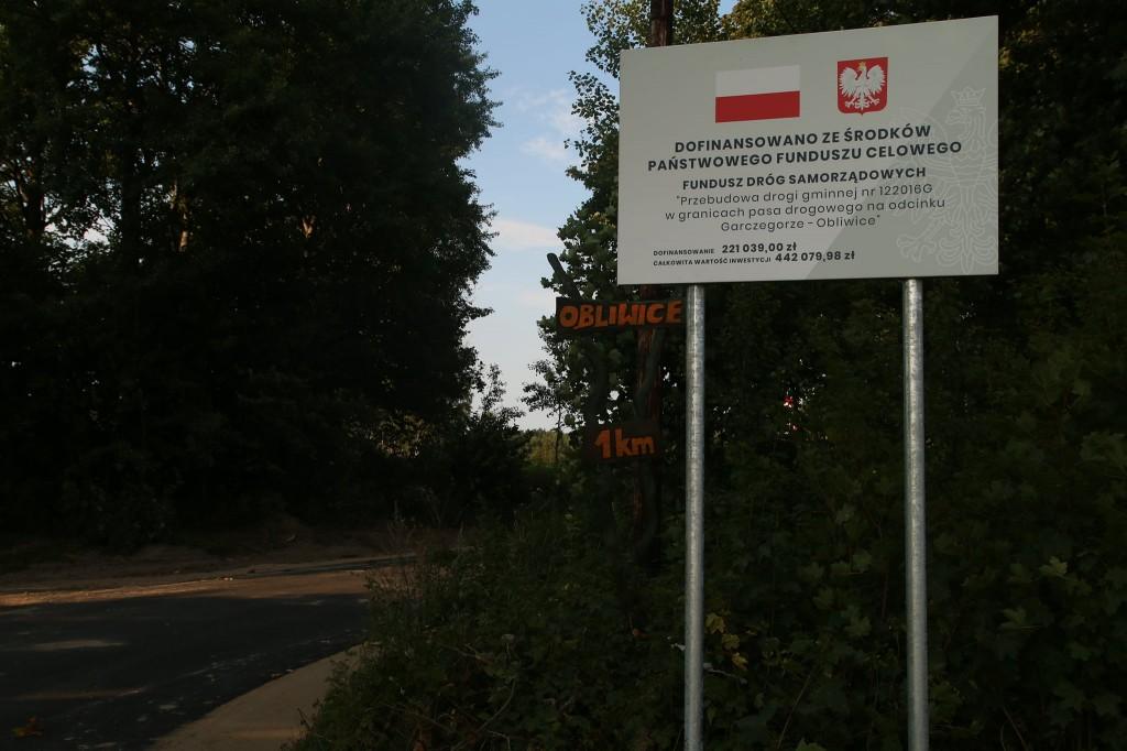 Przebudowany odcinek drogi prowadzący przez las. Przy drodze ustawiona tablica informacyjna z inwestycji, a na niej komunikat o dofinansowaniu z Funduszu Dróg Samorządowych. Na tablicy znajduje się flaga i godło Polski.