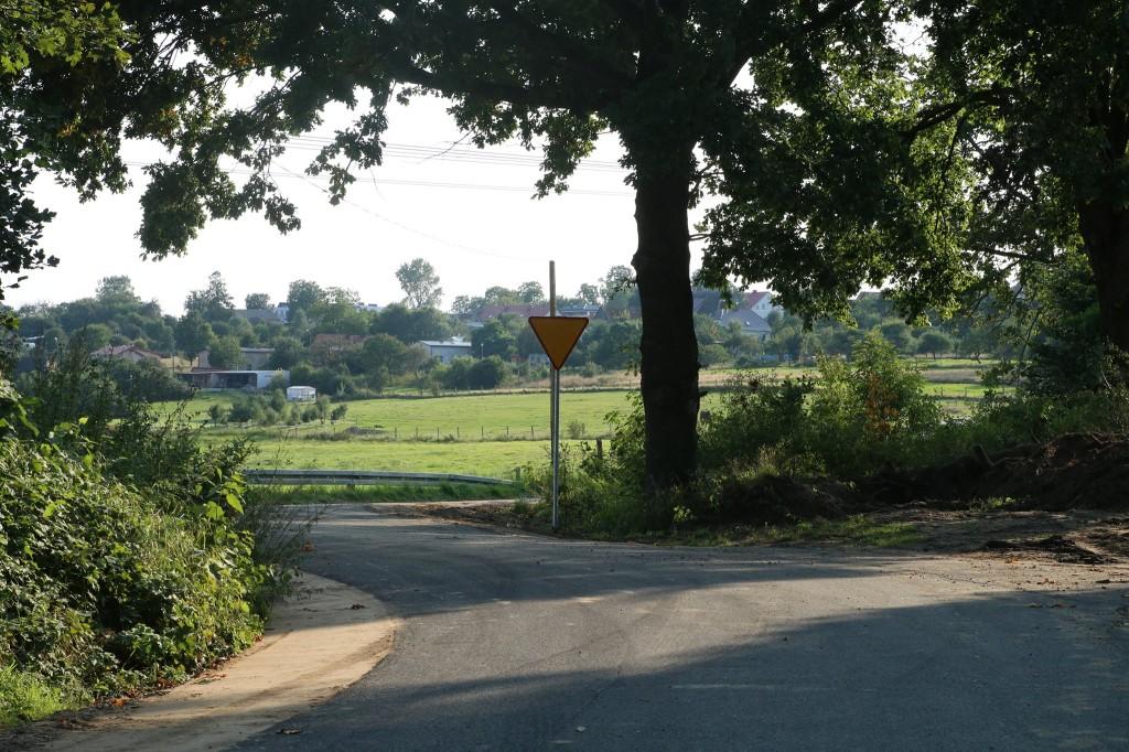 Przebudowany odcinek drogi prowadzący przez pola. Zadrzewione pobocza. W tle zabudowania gospodarskie.