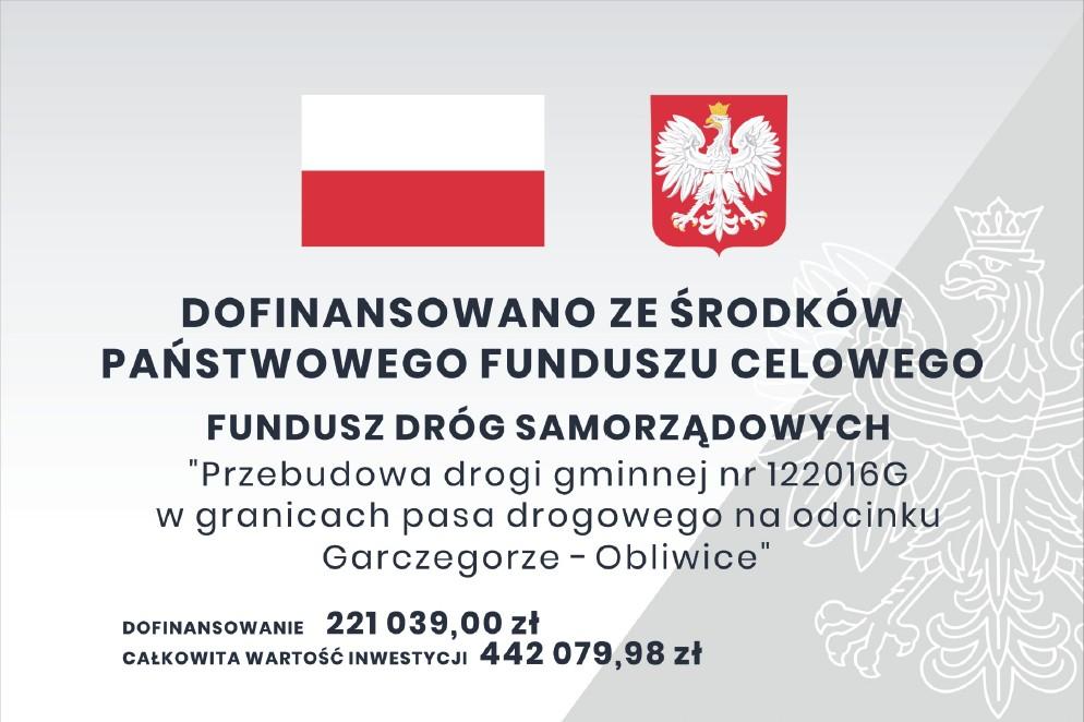 Tablica informacyjna zawierająca nazwę projektu i komunikat o dofinansowaniu inwestycji z Funduszu Dróg Samorządowych. Na tablicy znajduje się flaga i godło Polski.