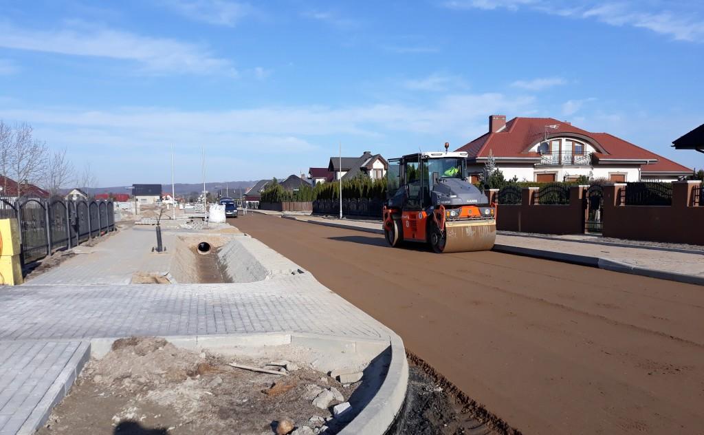 Kolejny etap budowy drogi. Chodnik ułożony z kostki brukowej, krawężniki ułożone, rowy melioracyjne wyłożone ażurowymi płytami z betonu. Walec wałujący kolejną warstwę podbudowy drogi, przygotowującą do wylania asfaltu. W tle zabudowania domów jednorodzinnych.