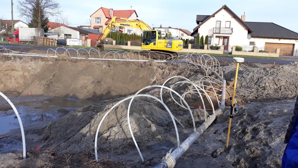 Początkowy etap budowy drogi. Urządzenia drenujące grunt. Pracująca koparka. W tle zabudowania domów jednorodzinnych.